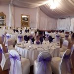 White chair covers and violet organza sashes for wedding, Rendezvous Hotel