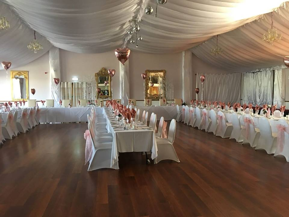 U shaped wedding set up with white chair covers and pink sashes Rendezvous Hotel