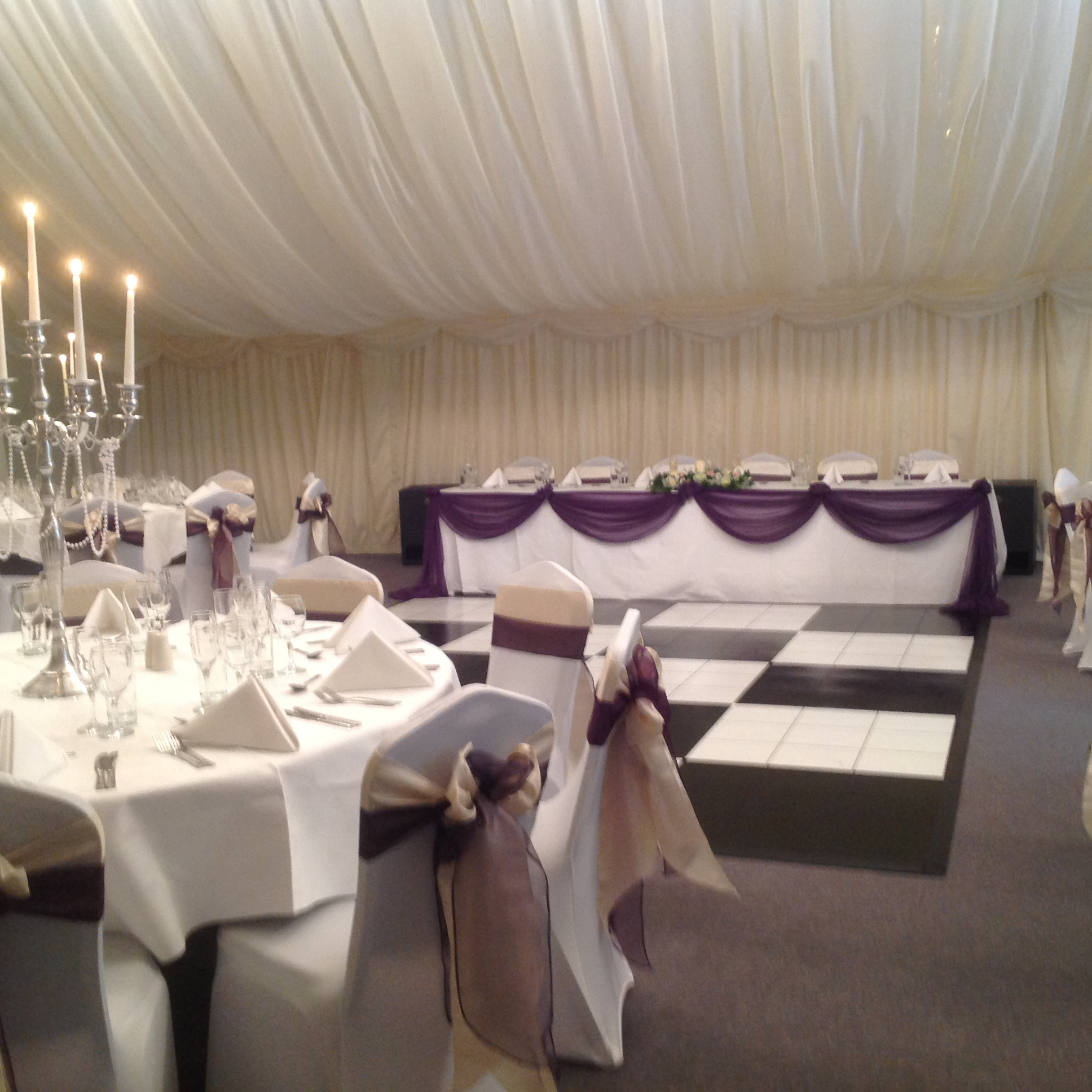 Wedding breakfast at Halfway House, Baildon, white chair covers, top table swagging, candelabra centrepiece. Ivory taffeta and plum sash