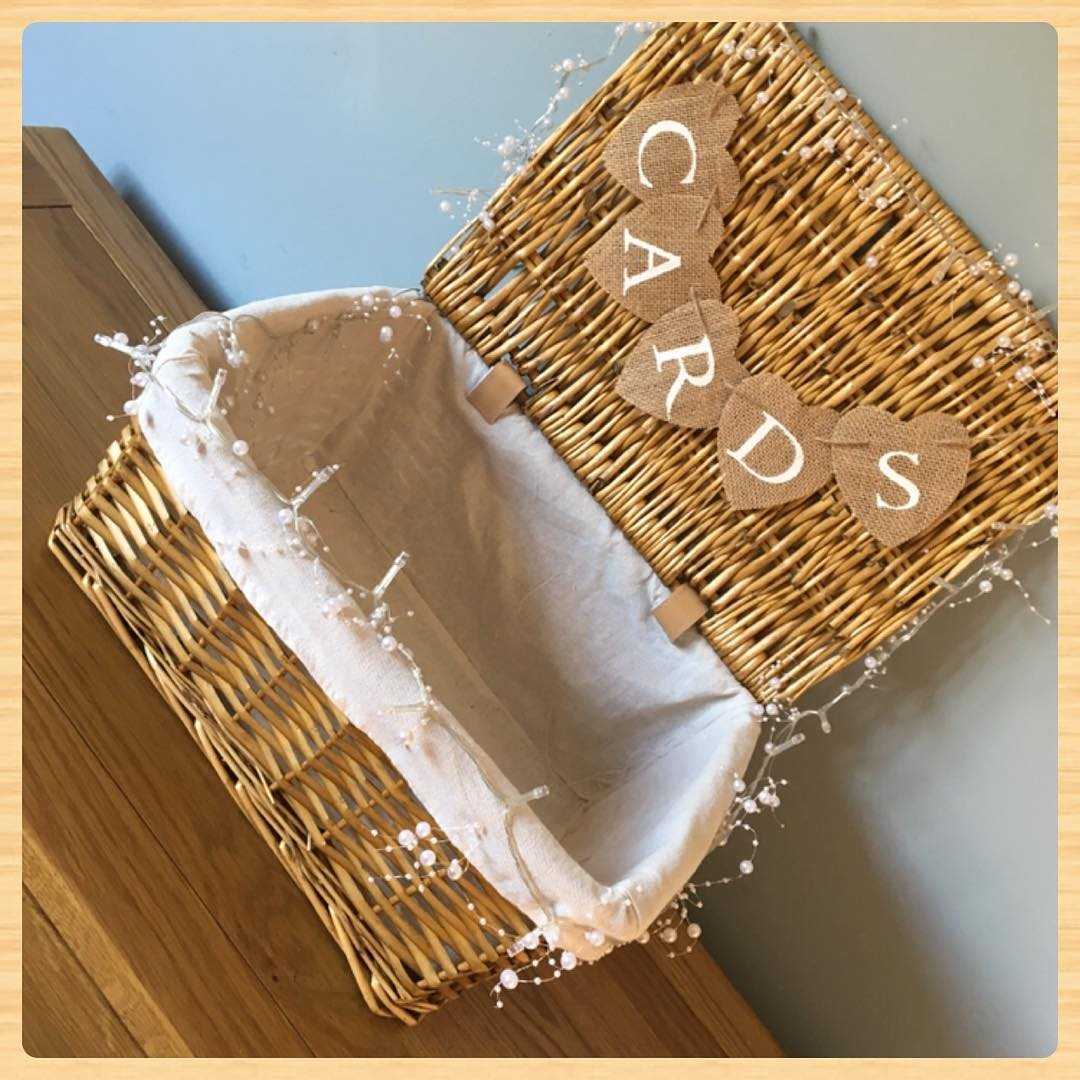 Wicker basket for cards from wedding guests, with lights and bunting