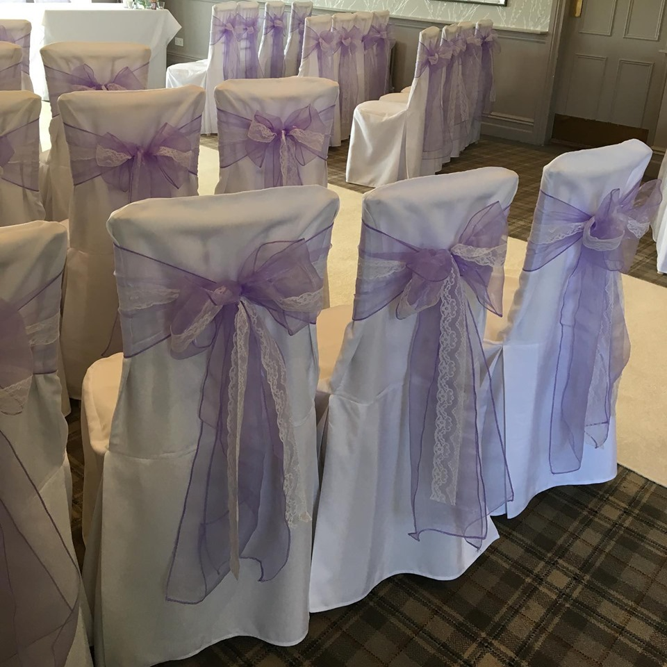 White loose cotton wedding chair covers with lilac and white lace bows at Devonshire Fell