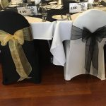 New years eve ball with black and white chair covers and gold and black sashes