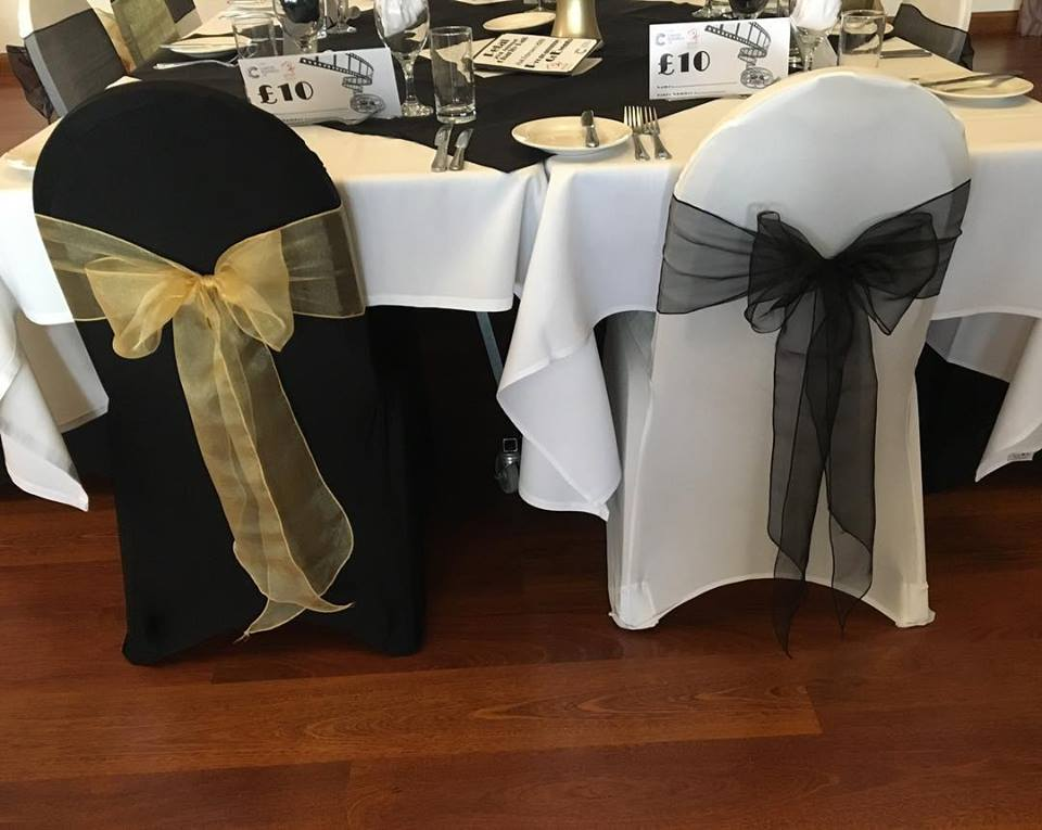 Ball event decor, black and white chair covers with gold and black sashes Rendezvous Hotel