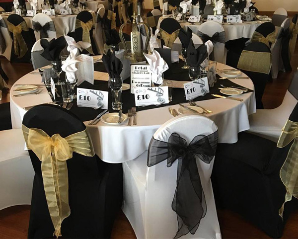 Black and white chair covers, gold and black sashes, new years eve ball Rendezvous Hotel
