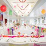 Rainbow wedding, white chair covers, Cavendish Pavilion, pink, yellow, green, purple sashes