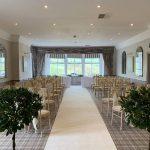 Wedding ceremony with ivory aisle carpet, bay trees and ivory taffeta sashes on chiavari chairs, Devonshire Fell
