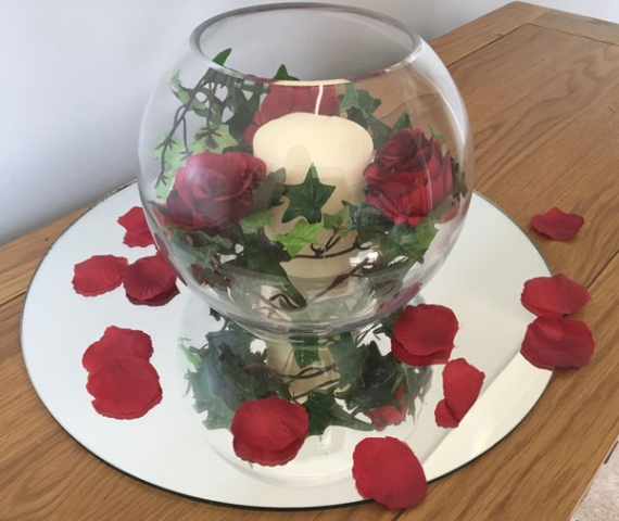Fishbowl centrepiece on mirror with scatter petals, candles and ivy, wedding or event