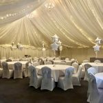 Silver bows on white chair covers for holy communion celebration at Halfway House, Baildon