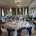 White chair covers with grey and plum bows for a corporate event