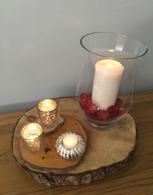 Hurricane vase with candle and votives on wooden block for wedding centrepiece