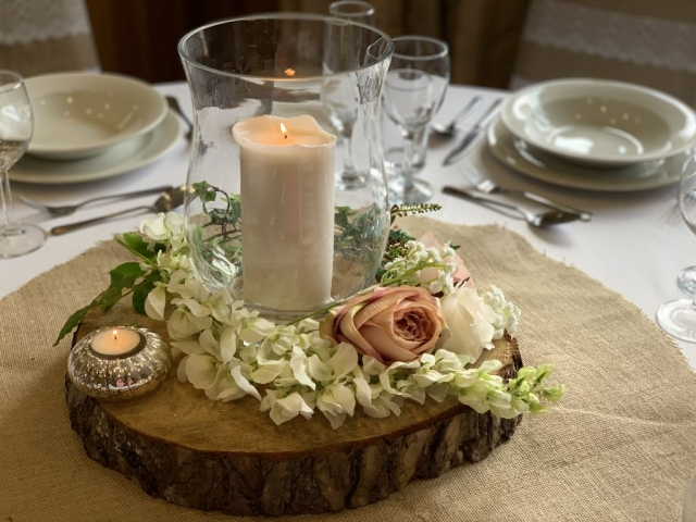 Wooden block, hurricane vase and candle with flowers for rustic wedding centrepiece