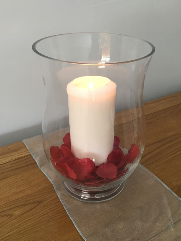 Hurricane vase with church candle and petals, wedding centrepiece