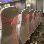 White chair covers with pink sashes, top table, wedding breakfast at Oultin Hall, Leeds