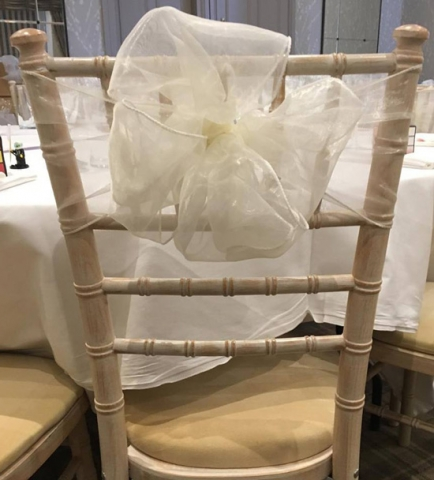 Ivory organza double bow on a chiavari wedding chair at Devonshire Fell, Burnsall