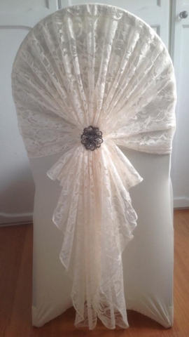 White lace hood and brooch over a white chair cover, wedding chair decor