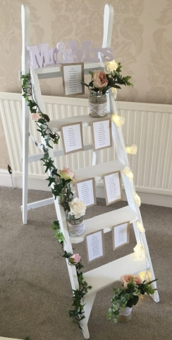 White vintage ladder for wedding seating plan with lights and flowers