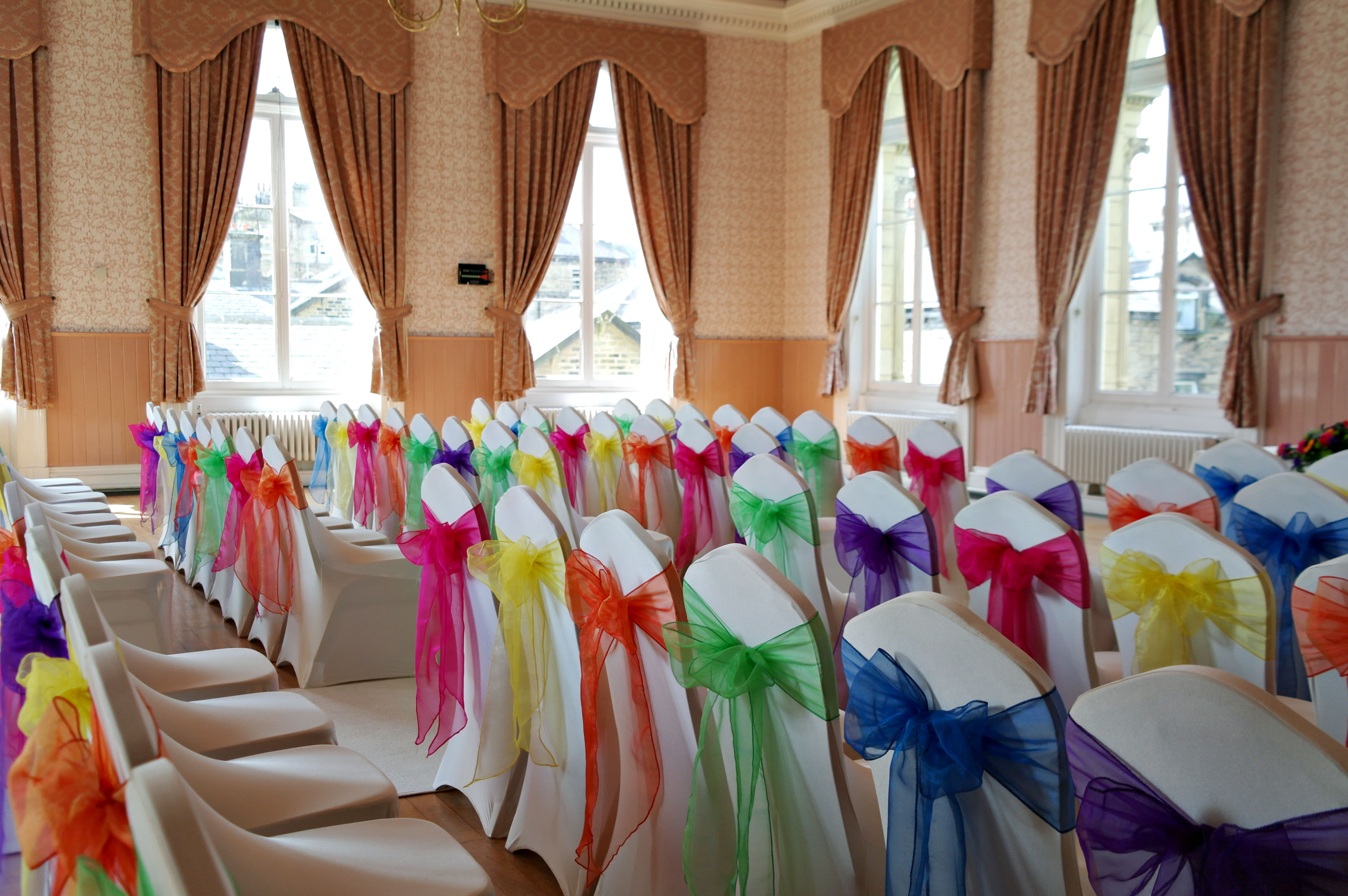 Rainbow wedding. Victoria Hall, Saltaire, white chair covers, purple, blue, green, orange, yellow and pink bows