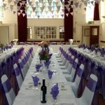 Village hall wedding with white chair covers and purple sashes, bunting, long tables