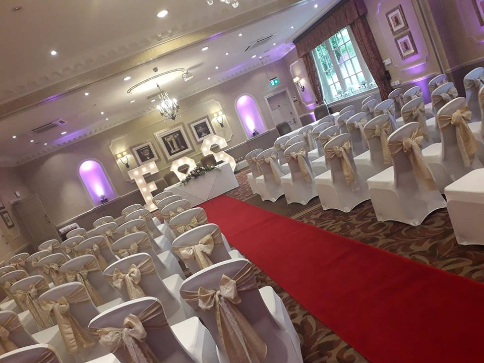 Wood Hall Spa Hotel, red aisle carpet, white chair covers, ivory taffeta and white lace sashes