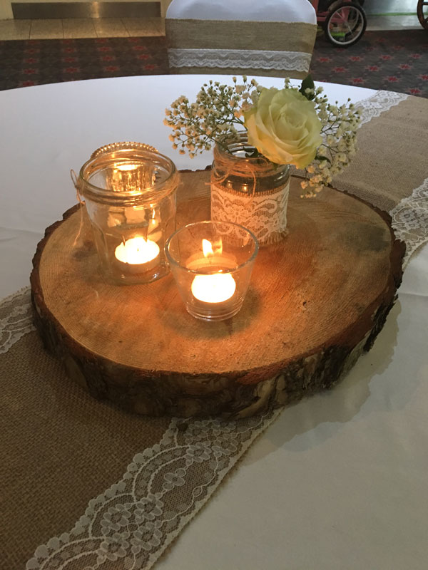 Wooden log with jars, flowers and candles, with hessian and lace for rustic wedding centerpiece