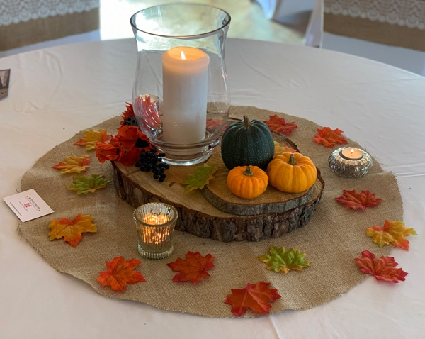 Autumn hurricane vase on wooden log for rustic wedding centrepiece