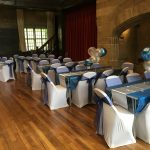 Venue styling with white chair covers and navy blue sashes for christening in Clay House, Halifax
