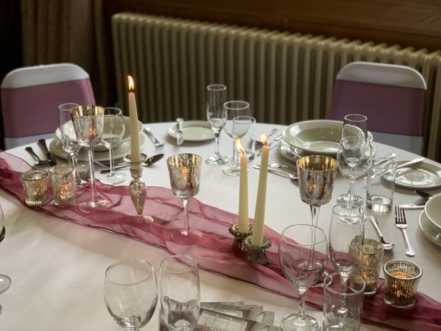 Candlesticks, tealights, elegant centrepiece on ruffle table runner