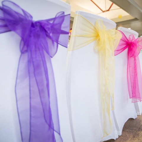 White chair covers; pink, purple and yellow bows. carnival theme wedding, Cavendish Pavilion