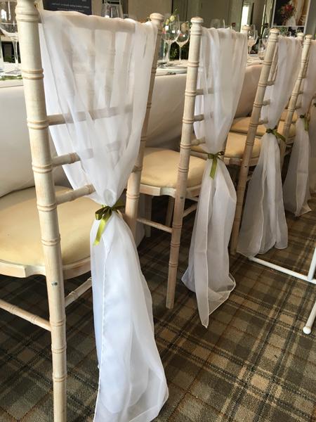 White chiffon drape on chiavari chair, tied with green satin ribbon for wedding at Devonshire Fell