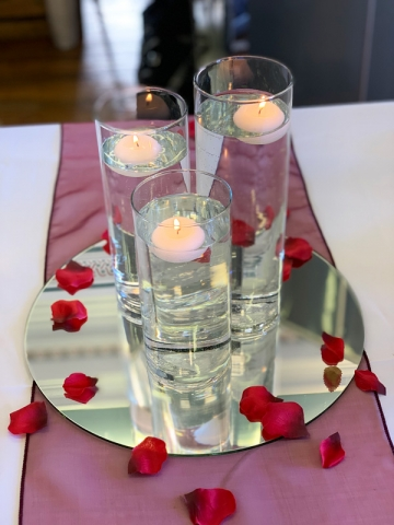 Three cylinder vases with floating candles, mirror and scatter petals for wedding centrepiece