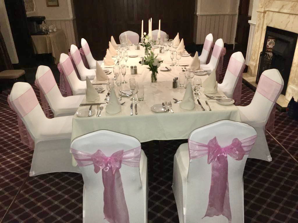 Ivory chair covers with lavender pink bows, intimate wedding with candelabra centrepiece. Oakwood Hall, Bingley