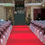 White chair covers with silver taffeta sashes, red aisle carpet Kings Hall, Ilkley