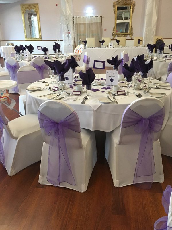 Celebration decor with white chair covers and lilac sashes,