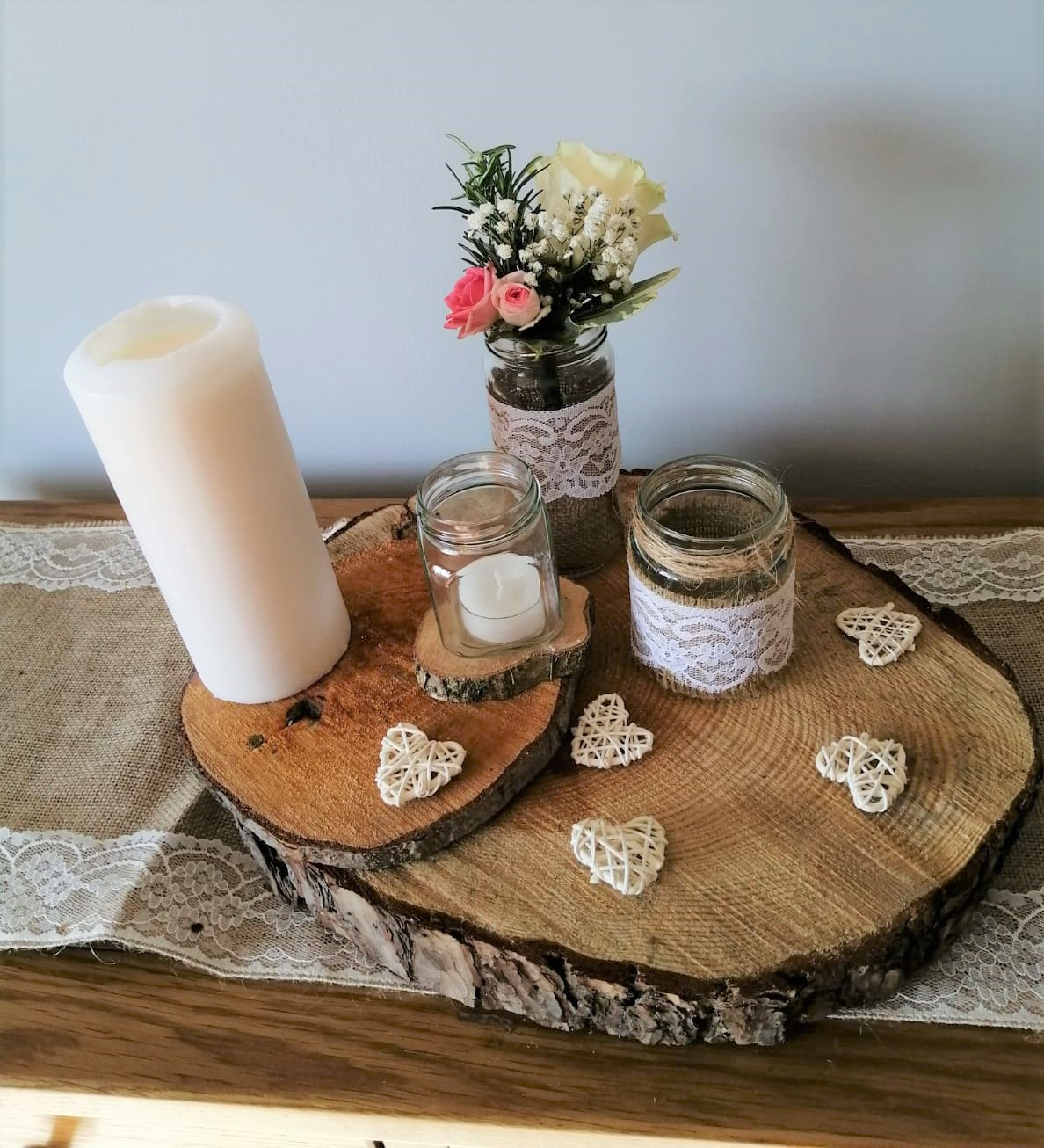 Rustic wedding centrepiece with logs, jars, candles and flowers, hessian and lace
